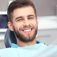 Man with brown hair smiling after getting cosmetic dentistry