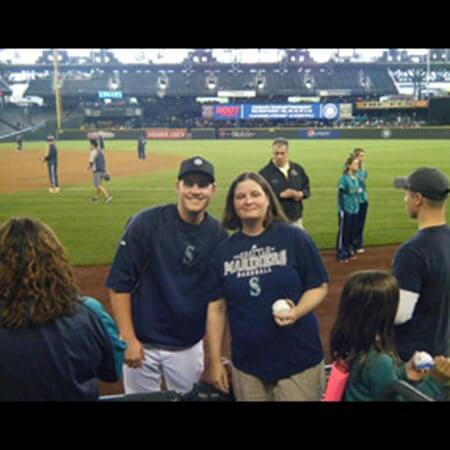 Team member posing with Mariners player