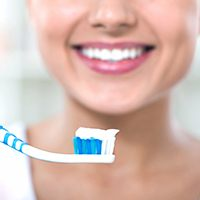 Smiling woman with toothpaste on toothbrush