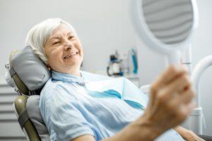 older woman admiring her smile with dental implants in Bellingham