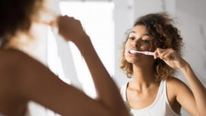 Person brushing teeth with toothbrush from dentist in Bellingham